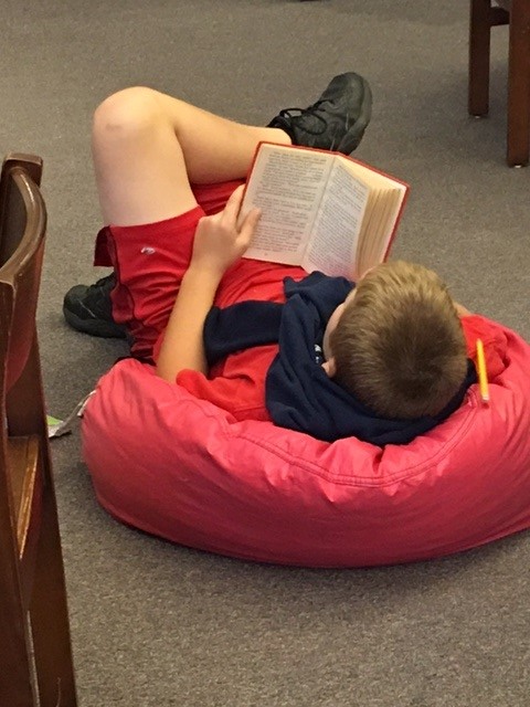 Student reading in bean bag chair.