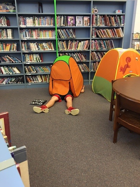 Student reading in tent.