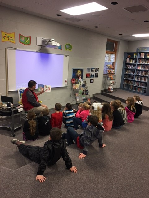Mr. Fischer reading a story to students.