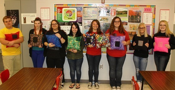 High School students display pillows they sewed.