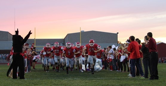 2015 Football players storm field at dusk with fans.